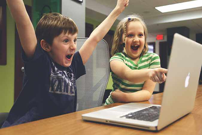 Children excitedly staring at a computer screen