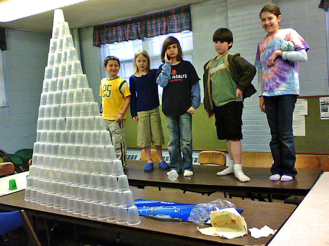 Students standing by stacked cups