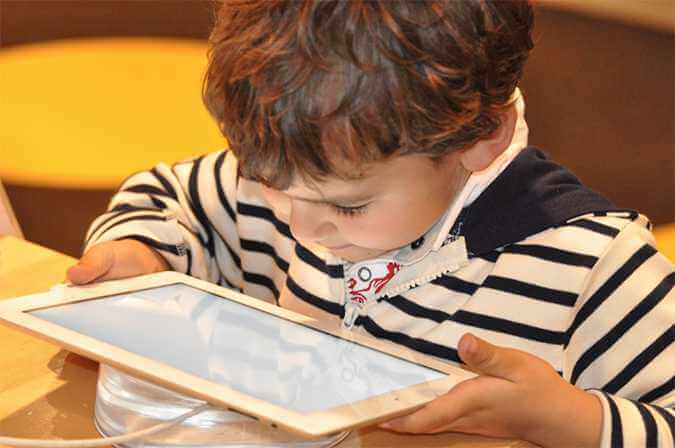 A child looking at a tablet device
