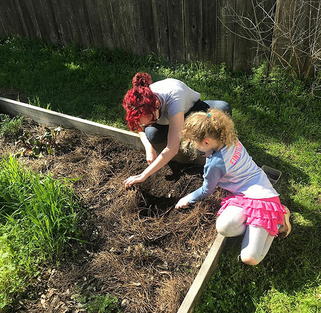 An adult and child gardening