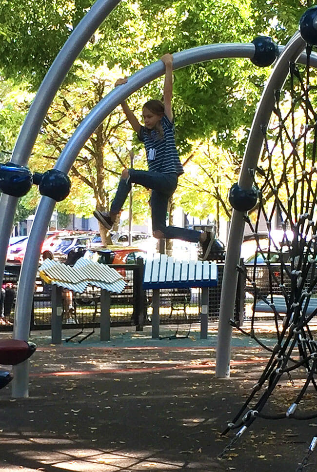a young person climbing on a jungle gym
