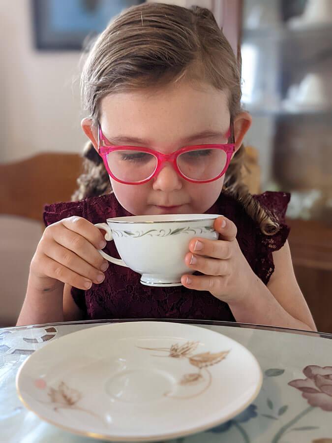 Ребенок пьет из чайной чашки